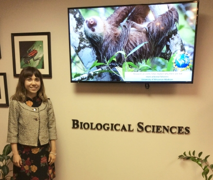 Photo of Nicolle in front of a sign for the Biological Science Directorate with a tv monitor behind her displaying a photo of a sloth.